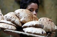 A child balancing a tray of bread On his shoulder, which he has just bought from a bakery in Cairo.