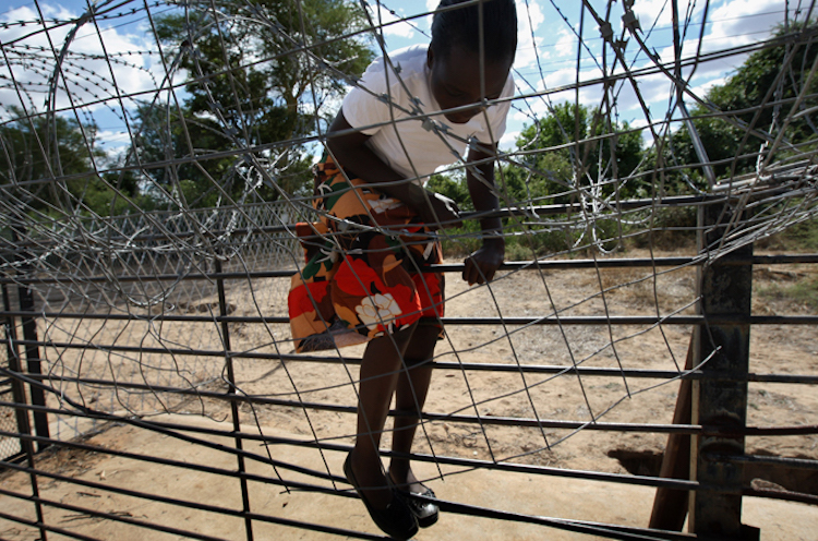 Photo: An unidentified child trying to skip the border fence into South Africa.  Credit: Aljazeera