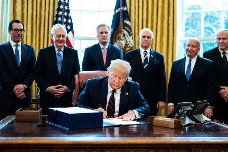 Photo: President Trump participates in a signing ceremony for a two trillion dollar coronavirus relief bill in the Oval Office at the White House in Washington, DC on March 27, 2020. Credit: Pool/ABACA/ABACA/PA Images