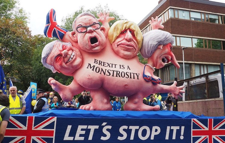 Photo: At the front of a demonstration against Brexit in Manchester a float showed a multi-headed chimera with the faces of Theresa May and three leading Brexit campaigners: then Foreign Secretary Boris Johnson, Environment Secretary Michael Gove and Brexit Secretary David Davis. The photo was taken by Robert Mandel on October 1, 2017. CC BY 4.0