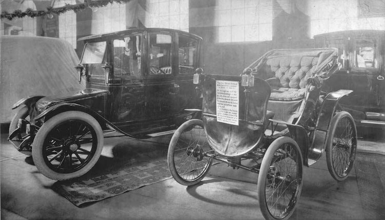 Photo: An electric vehicle and an antique car on display at a 1912 auto show in Toronto, Canada. Credit: William James. Source: Wikimedia Commons.