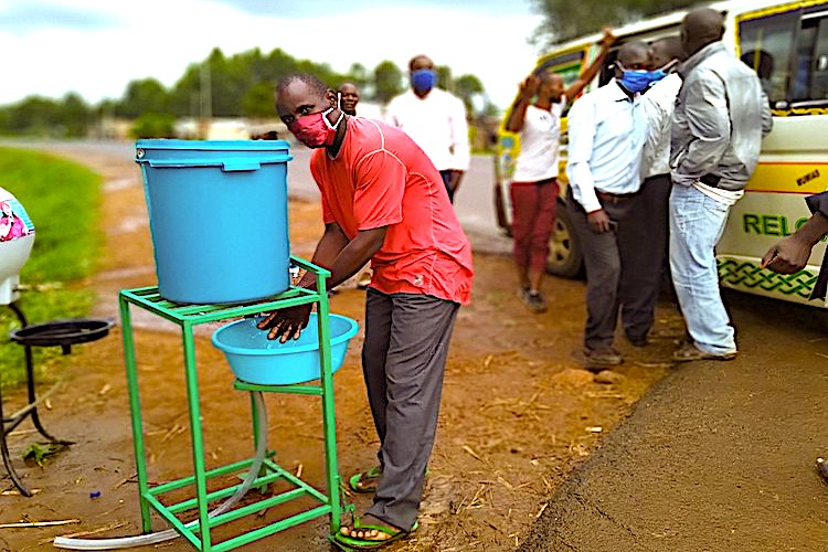 Photo: A passenger washing hands using  the new device before boarding a public  service vehicle at Muangatsi Market Centre Bus Stage, Busia County, Kenya. Credit: Kevin Wafula.