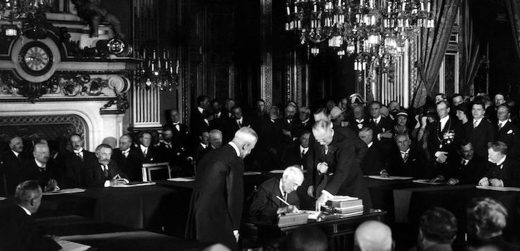 Photo: U.S. Secretary of State Frank B. Kellogg signs The Kellogg Briand Pact (or Pact of Paris) for Renunciation of War as an Instrument of National Policy on August 27, 1928 at the ministry of foreign affairs in Paris. Background French Foreign Affairs Minister Aristide Briand. Credit: AFP/Getty Images.
