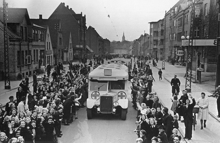 Photo: As part of Count Folke Bernadotte action, Danish Red Cross buses drive through Odense on the way to Sweden, carrying Danish prisoners from German concentration camps April 17, 1945. CC BY-SA 2.0.